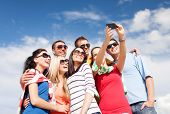 summer, holidays, vacation, happy people concept - group of friends taking picture with smartphone