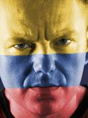 Closeup of young colombian supporter face painted with national flag colors