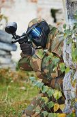 foto of paintball  - Adrenalin paintball player in protective uniform and mask aiming gun before shooting in summer - JPG