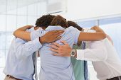 stock photo of huddle  - Rear view of business team with heads together forming a huddle - JPG