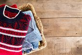 stock photo of wooden basket  - Wicker laundry basket filled with clean fresh washed winter clothes viewed from overhead standing at an angle on rustic wooden boards with copyspace on the right - JPG