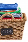 image of neat  - Close up view of washed fresh clean clothes neatly folded and stacked in a rustic wicker laundry basket with a handwritten label saying  - JPG