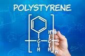 Hand with pen drawing the chemical formula of polystyrene