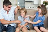 picture of tickle  - Father and daughter tickling boy sitting on sofa at home - JPG