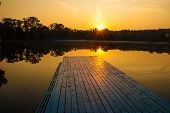 stock photo of dock a lake  - orange sunset sunrise lake boat and trees - JPG