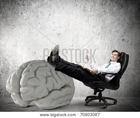 Young handsome businessman sitting in chair and reading book