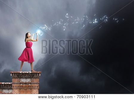 Young woman in red dress on building top playing fife