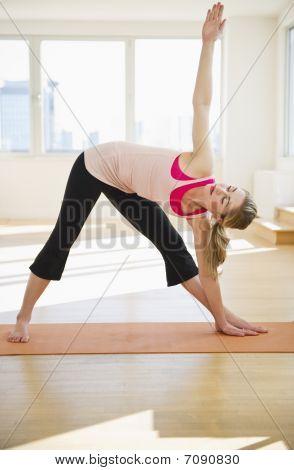 Woman Doing Yoga On Mat In Studio