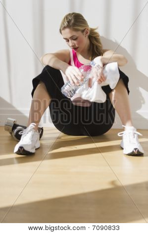 Female Sitting Against Wall In After Workout