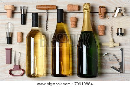 High angle shot of Wine and Champagne bottles surrounded by accessories such as corkscrews, stoppers, pourers and corks. Horizontal format on a rustic white wood table.