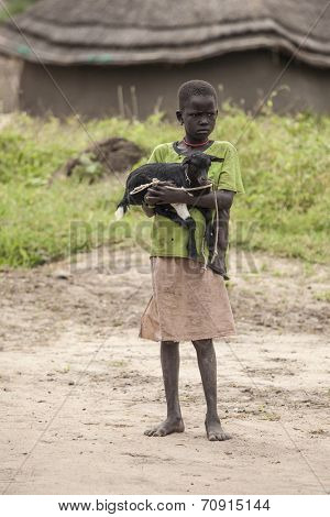 PANWEL, SOUTH SUDAN-NOVEMBER 2 2013: Unidentified child holds a baby goat in the village of Panwell in South Sudan