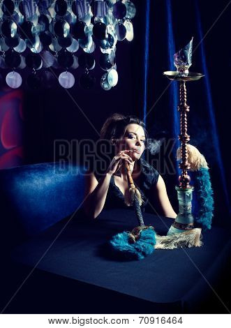 Beautiful woman smoking hookah in nightclub