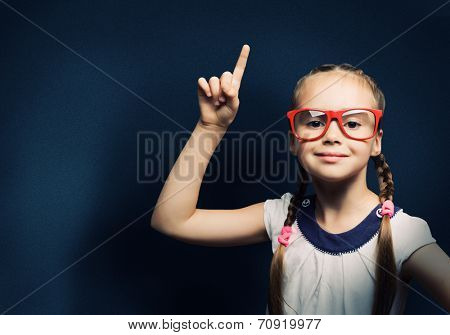 Cute school girl in glasses standing at blackboard
