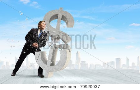 Young businessman breaking stone dollar sign. Currency concept