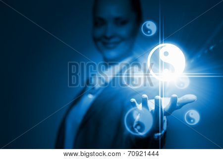 Businesswoman holding yin yang symbols in palm