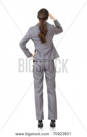 Rear view of Asian businesswoman looking far away, full length portrait isolated on white background.