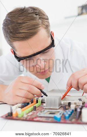 Technician working on broken cpu with soldering iron in his office