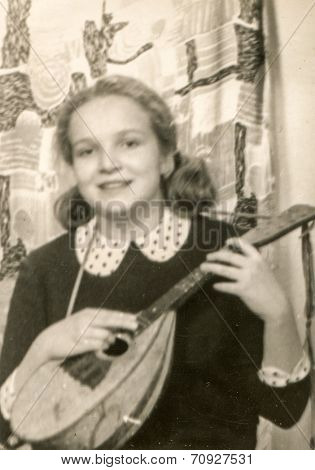 Vintage photo of little girl playing on mandolin (sixties)