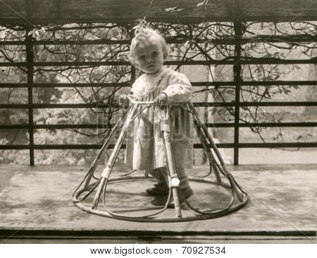 Vintage photo of little girl in a baby walker (fifties)