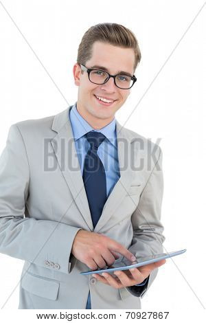 Nerdy businessman using his tablet pc on white background