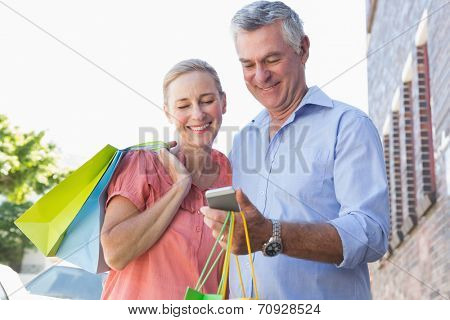Happy senior couple looking at smartphone holding shopping bags on a sunny day