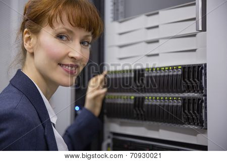 Pretty technician smiling at camera beside server tower in large data center
