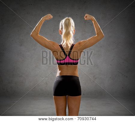 fitness, sport and people concept - smiling athletic woman in sportswear form back over concrete wall background