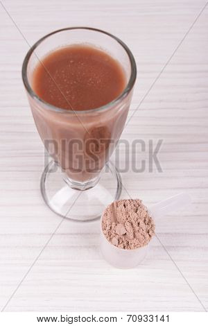 Whey protein powder and chocolate protein shake on wooden background