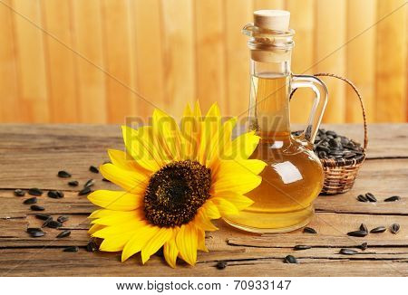 Sunflower with seeds and oil on wooden background
