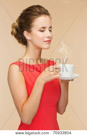 leisure, happiness and drink concept - smiling woman in red dress with cup of coffee