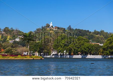 View on Kandy lake and big Buddha on top of the hill. Kandy is home of The Temple of the Tooth Relic, one of the most sacred Buddhist places of worship.