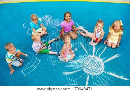 Group of children draw with chalk on playground