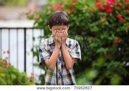 Young boy covers his eye