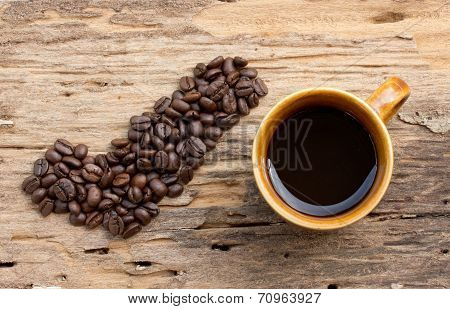 Checkmark From Coffee Beans And Cup Of Coffee On Wood Background