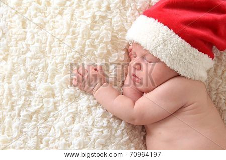 Christmas baby wearing a Santa hat
