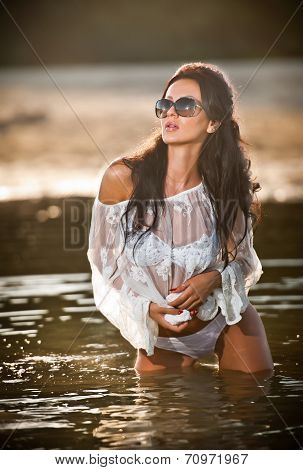 Young sexy brunette girl in wet white blouse posing provocatively in water. Sensual attractive woman