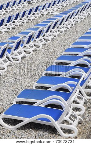 Blue Sunbeds On Pebble Beach