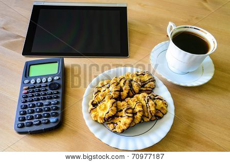 Workplace With Tablet Pc, Calculator, Cup Of Coffee And Cookies