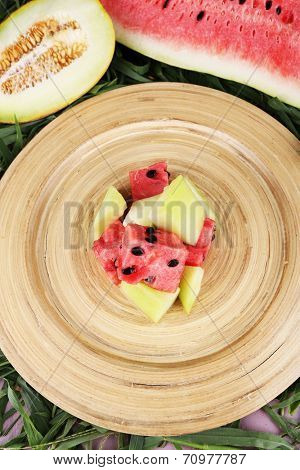 Melon and water melon on bamboo plate on grass background