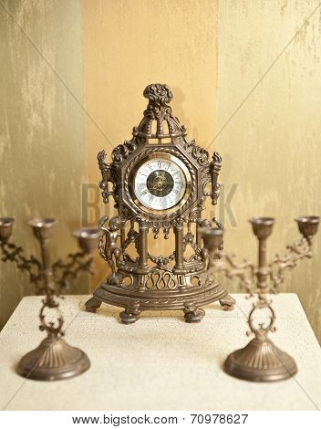 Golden vintage metallic clock with two candlesticks for three candles on white table
