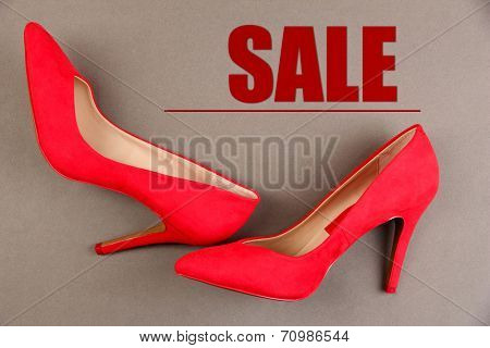 Concept of discount. Beautiful red female shoes, on grey background