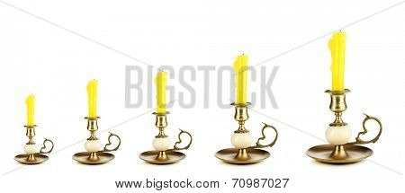 Evolution concept.Old candle holders with candle isolated on white