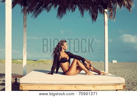 beautiful fashion woman posing on sandy beach in black bikini and shirt sitting on white beach bed under sunshade full body shot