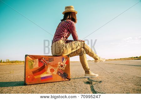 Traveler Sits On Suitcase With Stamps Flags