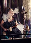 foto of hookah  - Beautiful woman smoking hookah in nightclub - JPG