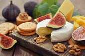 stock photo of walnut  - Camembert cheese with walnuts and fresh figs on wooden background - JPG