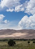 picture of dune  - Detailed shot of the shadows on the dunes at Great Sand Dunes National Park in Colorado with the tiny people walking on the sand giving some scale to the dunes - JPG