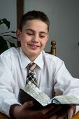 stock photo of scriptures  - A young man is studying his scriptures - JPG