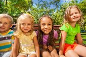 stock photo of sitting a bench  - Four little kids happy and smiling sitting on the bench and looking close to wide angle lens with funny smiling faces - JPG