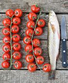 stock photo of mullet  - raw mullet with cherry tomatoes on wooden table - JPG